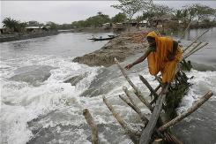 A woman crosses a bamboo bridge made over a breached dam caused by cyclone Aila, which hit Bangladesh in June. Natural disasters and severe weather caused insurers above-average losses of $11 billion in the first half of this year.