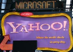 A news ticker flashes a headline about Microsoft above a billboard for Yahoo in New York City.