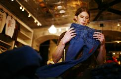 Clerk Jason Popps folds jeans at the Lucky Brand Store at Tysons Corner Center in McLean, Va. Sales of traditional jeans are strong, but high-end denim sees declines.