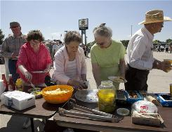 Members of the public help themselves to hamburgers during a celebration at Gateway Motors, a recently reinstated dealership in Broken Bow, Neb. People in this small town and others across the country think their political savvy and Americana-heavy marketing may have convinced General Motors to have a change of heart.