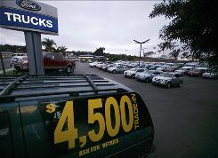 "An old vehicle sits on a Ford dealership lot in Encinitas, Calif., advertising the governments ""Cash for clunkers."""