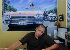 Nick Nonis, a broker at Torelli Realty in Costa Mesa, Calif., works at his desk while on hold with a mortgage company. Nonis says that he can be on hold for two to three hours before getting through to a representative. 