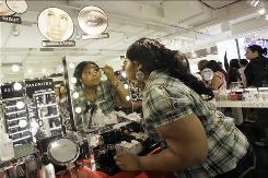 Sheika Smith, 26, of the Bronx, applies eye make up at the Sephora counter of the new JC Penney store in the Manhattan Mall. Retailers are reporting sluggish sales for July, especially at mall-based chains as shoppers' worries about jobs escalate.