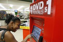 Aisha Smith chooses a DVD at a Redbox movie-rental unit in a north Seattle grocery store.