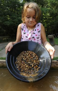 "Cathryn Struck, 8, pans for gold at Reed Gold Mine in Midland, N.C. She and her dad, William, found three small flakes of gold. As she left, Cathryn said, ""It's probably worth a fortune."""