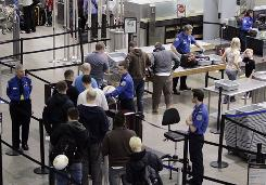 Fliers line up in March at the TSA security check at Minneapolis-St. Paul airport. A congressman suggests putting a template on security X-ray machines to weed out oversize carry-ons.