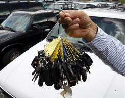 Sales manager Mark Hranicky of Lee Toyota in Topsham, Maine, holds up keys Aug. 24 to some of the 90 cars traded in under the government's cash for clunkers program.