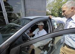 Mostafa Ellaida, right, shows a Toyota Corolla to Nicholas Sasso at Bay Ridge Toyota in New York earlier this month. Corolla was the top seller in the cash for clunkers program.