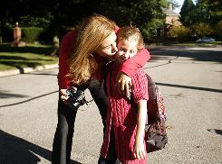 Leslie Fox kisses her youngest daughter, Samantha, 6, goodbye before she catches the bus for her first day of school on Aug. 31 in New Albany, Ohio. The family looks forward to back-to-school shopping.