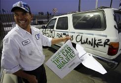 In Los Angeles, Elder Rodriguez tears down an ad banner as cash for clunkers ends Aug. 24.