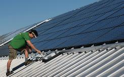 Wayne Irwin of Pure Energy Solar works on a solar panel system in Gainesville, Fla.