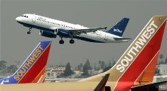 A JetBlue plane flies over a pair of Southwest jets at Bob Hope Airport in Burbank, Calif. A 5-hour delay of a Continental Express flight has renewed calls for a time limit on tarmac delays.