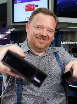 Anthony Wood holds a Roku Set-top box and its remote. The Netflix player by Roku enables Netflix subscribers to stream movies and TV episodes from Netflix directly to the TV.