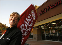 Melissa Carter, a former lawyer who decided to go into the pizza business, stands in front of her store in San Diego. She and her husband Andre recently opened the first CiCi's all-you-can-eat pizza buffet in California.