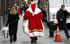 A man dressed as Santa Claus carries shopping bags as he walks along a sidewalk in New York City last year.
