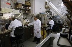 ETV Motors chief technology officer Arieh Meitav, center, stands in a laboratory at Bar Ilan University in Ramat Gan near Tel Aviv on July 16, 2009. ETV Motors, a private company that has raised some $12 million in investments, says it has found a way to make it commercially viable.