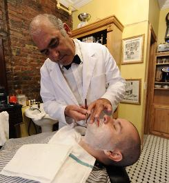 John Scala, owner of The New York Shaving Company, gets a shave from Ely Mirzakandov.
