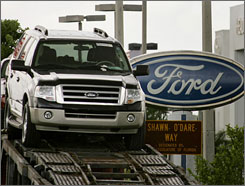 Ford vehicles are loaded onto a transporter outside a Ford dealership in Miami Lakes, Fla.