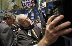 Trader Anthony Alvarino uses a phone post on the floor of the New York Stock Exchange on Aug. 12.