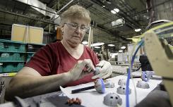Liz Maierle prepares a part for an orthopedic device at Biomet in Warsaw, Ind. Maierle has been with the company for 23 years.