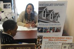 Carol Robinson, back, of Home Free in Hyattsville, Md., works on mortgage options with Viola Williams.