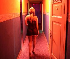 A prostitute walks  toward a room in a Berlin brothel.