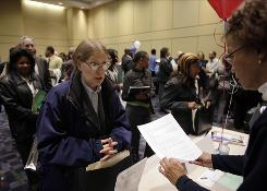S.J. Murray of Chicago, who was recently laid off from an IT job, talks to Frances Dobbins, right, of Advocate Health Care at a career fair in Chicago.