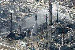 Firefighters work following a March 2005 explosion that killed 15 people and injured more than 170 at the BP Texas City refinery.