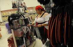 Mai Abdalla, dressed as a pirate, works at Party Mania's temporary Halloween shop in Vienna, Va.