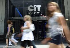 Passersby walk past the CIT logo in New York in July. The lender, whose clients are small and midsized businesses, has a debt of about $65B.
