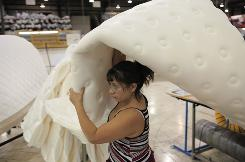 Roxana Barrios, who works at the Sealy facility in Williamsport, Md., carries a mattress panel. The facility uses lean-manufacturing techniques to be more cost-efficient.