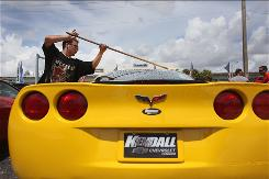 Nelson Ortiz washes a new Chevrolet Corvette on the sales lot at the Kendall Chevrolet at The Dadeland Mall in Miami. GM says Corvette tops the luxury sports car segment with nearly 28% of the market. 