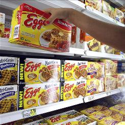 Store employee Jackie Steele straightens out the remaining boxes of Eggo frozen waffles on the shelf at Harvey's Supermarket in Tallahassee, Fla.