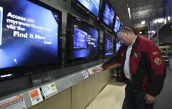 Doug Pongrazc checks out a large screen television at a Best Buy store in Elk Grove, Calif.