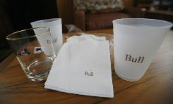 Napkins and glassware bear the name of Bernard Madoff's yacht, Bull. The boat was among several Madoff items auctioned off by the government Tuesday.