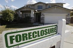 A foreclosure sign sits outside a home in Phoenix. Arizona has one of the highest foreclosure rates in the country.