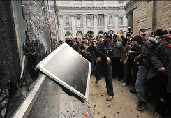 A protestor throws a computer terminal taken from a Royal Bank of Scotland office at the smashed windows of a branch of RBS in London on April 1, 2009.