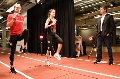 Nike CEO Mark Parker, right, watches as runners Kara Goucher and Dathan Ritzenhein perform stretch tests at Nike's research lab.