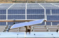 A solar energy panel is carried to be placed in a solar energy field during construction for the Sacramento Municipal Utility District in Rancho Cordova, Calif.,