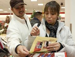 Chatrice Felix-Beza, of Renton, Wash., and husband Randy Beza go over their shopping list at Sears in the Westfield Southcenter Mall in Tukwila, Wash., on Black Friday, the day after Thanksgiving.