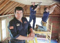Kaile Warren Jr., founder of the Rent-A-Husband handyman chain, poses, in 2002, in an addition his company was building.