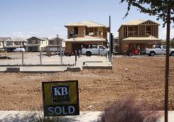 KB Home is building smaller homes nationwide. Here, a sold sign sits in front of homes being built in Gilbert, Ariz.