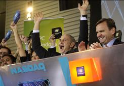 Chris Liddell, center, cheers after he pushed a button to begin the Nasdaq stock exchange trading day Oct. 22, the day Microsoft officially released the Windows 7 computer operating system.