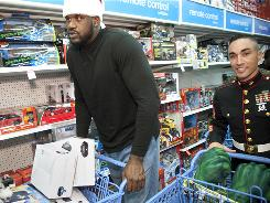 Shaquille O'Neal and Marine Kristopher Cortes load carts at a Toys R Us in Mayfield, Ohio, for the Marine Toys for Tots Foundation.