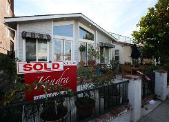 "A ""sold"" sign is shown outside a home in Long Beach, Calif."