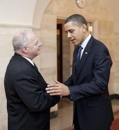 President Obama greets cybersecurity chief Howard Schmidt.