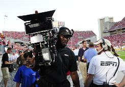 An ESPN cameraman carries a 3D camera at Ohio Stadium.