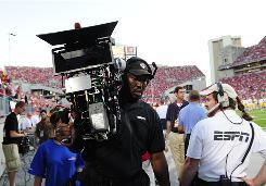An ESPN cameraman carries a 3D camera at Ohio Stadium.