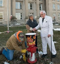Brazil, Ind., water company assistant supervisor Stoney Lalen adds the KFC and Fiery Grilled Wings logos to a fire hydrant as Mayor Ann Bradshaw shakes the hand of Colonel Sanders look-alike Bob Thompson.