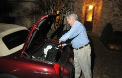 Frequent business traveler Bill Hall unloads his baggage after completing a one-day business trip to Tennessee.